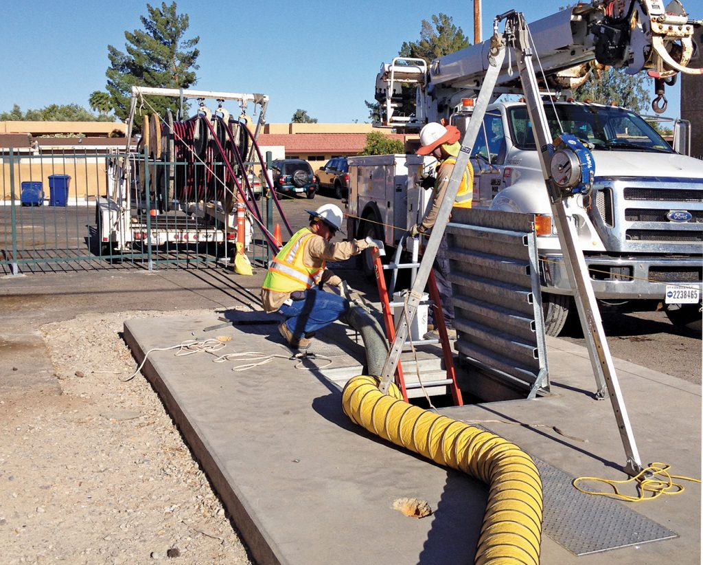 Crews pull communication lines from a guideway manhole along the Central Mesa Extension.