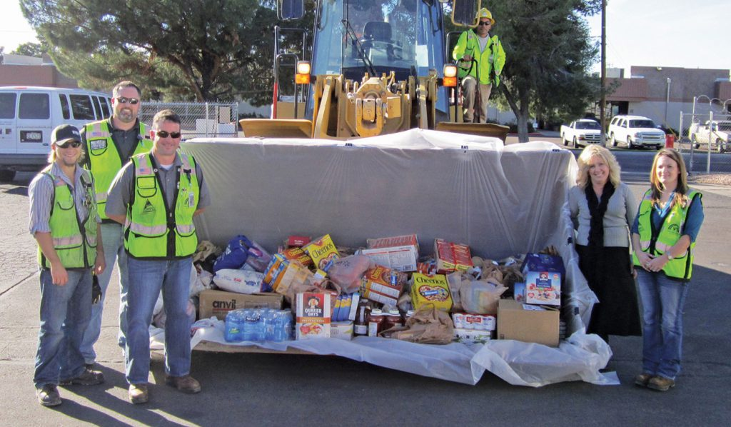 VTC employees with a bucketful of food collected during one of the many food drives throughout construction.