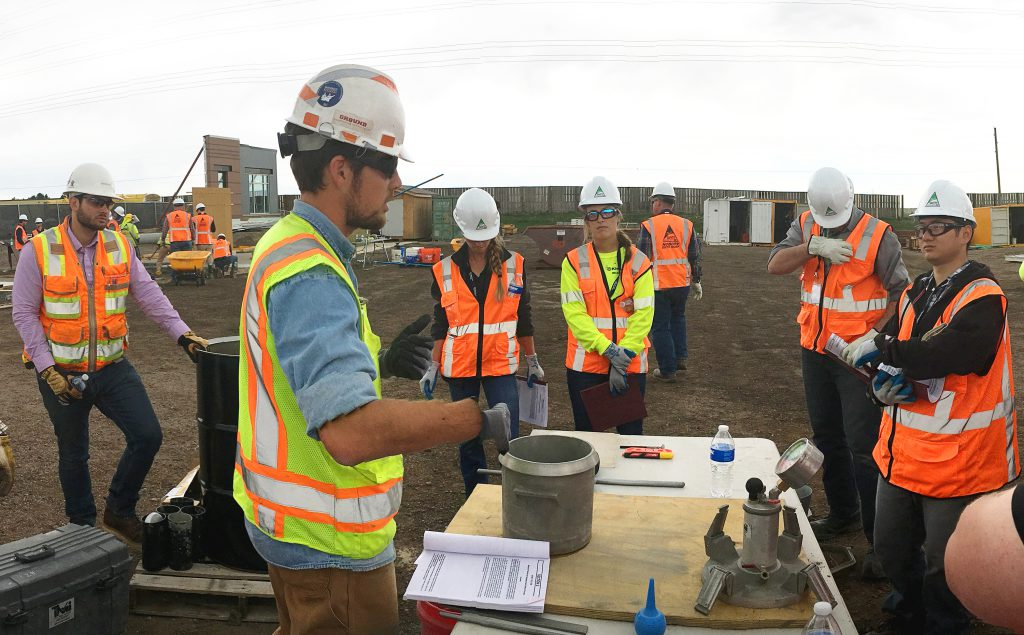 Employees observe a concrete material test demonstration during Concrete and Formwork Technical School.